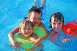 three kids floating in pool on floaty smiling at camera