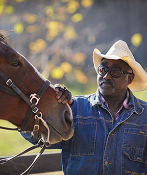African American man in straw cowboy hat and sunglasses petting a horse's nose.