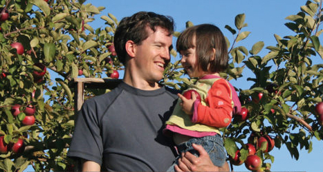 father holding daughter in apple orchard as she holds an apple
