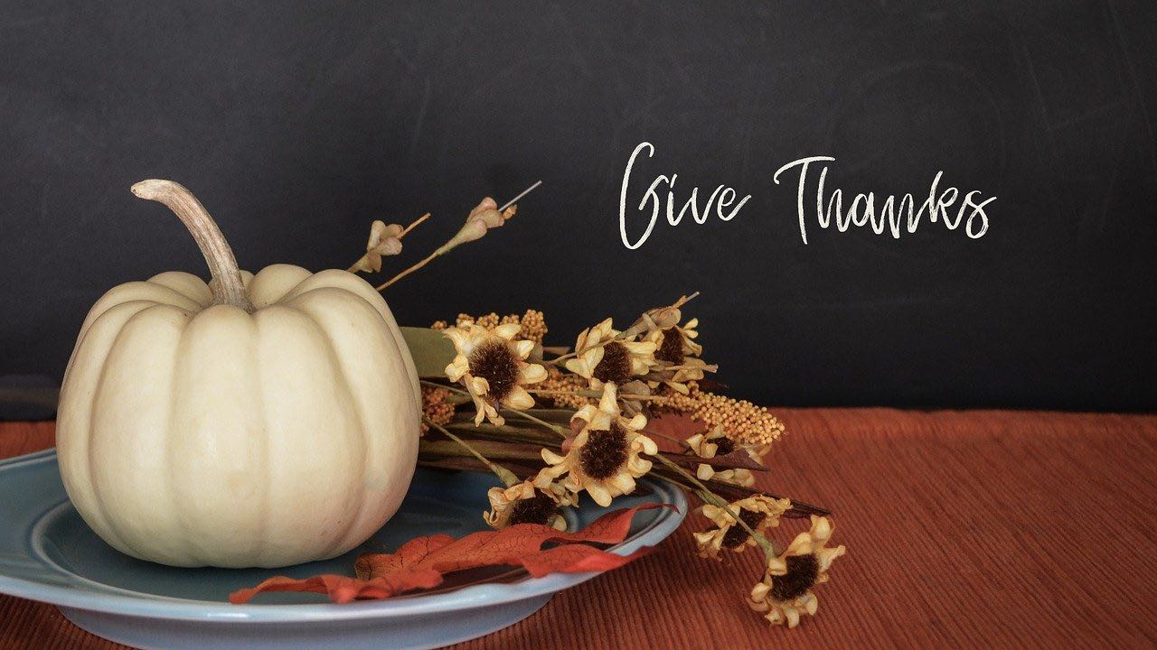 "digital white pumpkin and yellow flowers on table, ""give thanks"" written on wall in cursive"