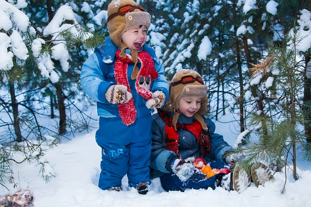kids in snow outfits playing in woods