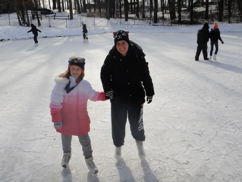 mother and daughter wearing winter clothes holding hands on ice skates with other people in background skating on frozen lake