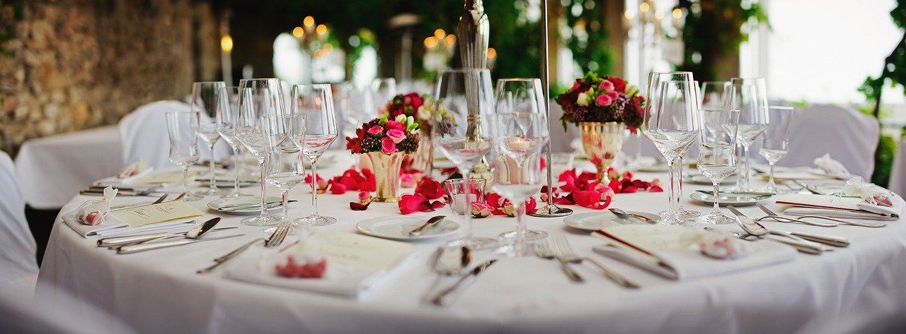 white table set with silverware and pink and red flower pedals
