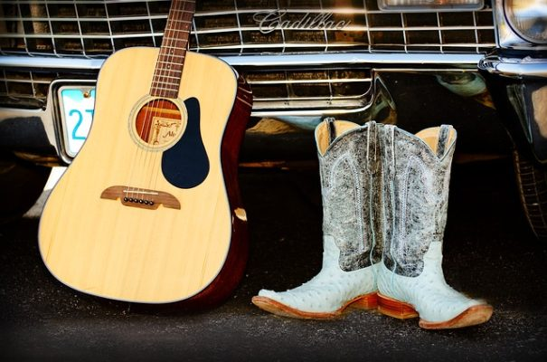 guitar and blue cowboy boots next to bumper of car