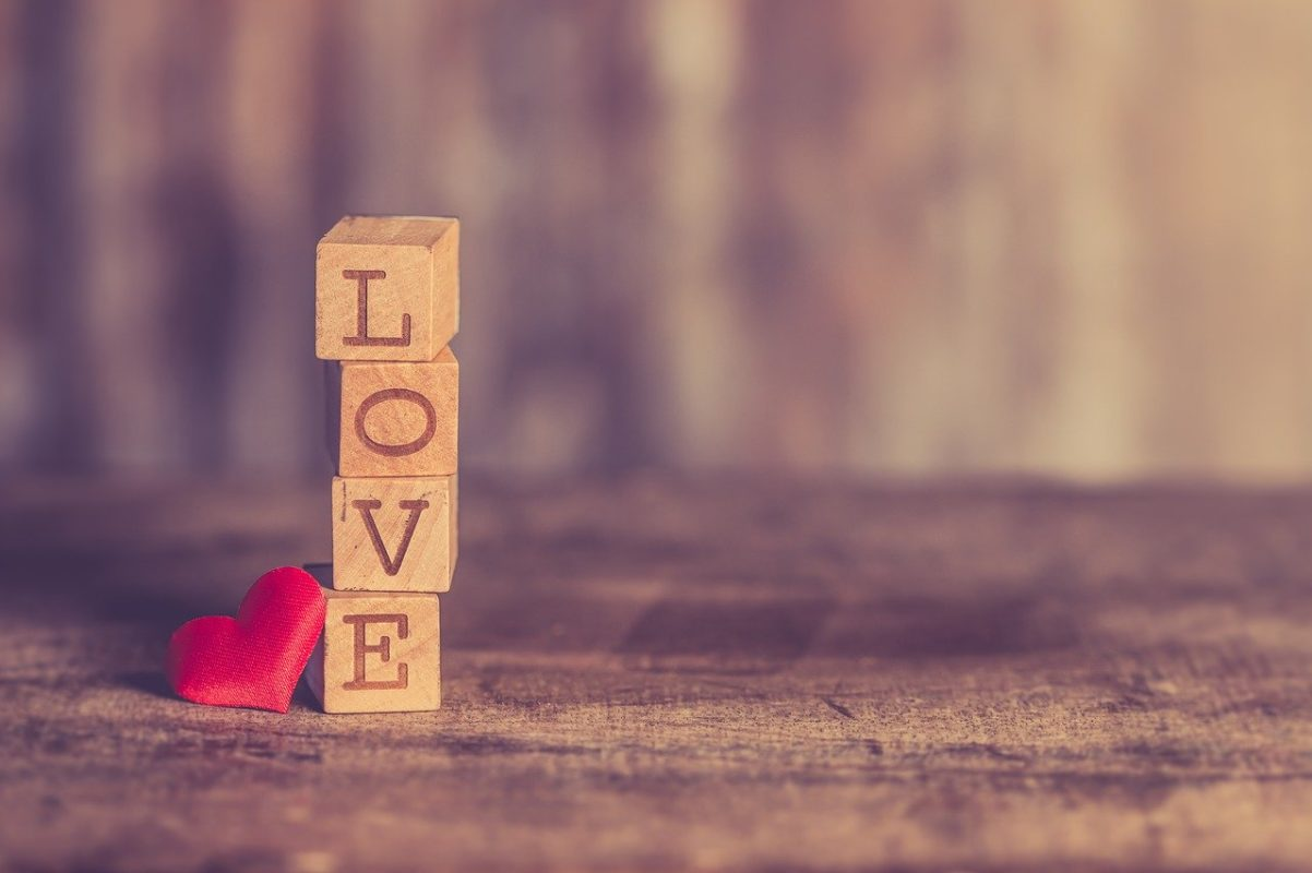 love spelled out in individual wooden blocks with a felt heart next to it on a wooden table
