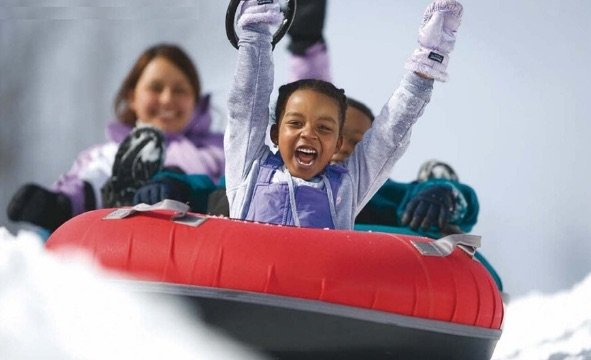 3 girls on snow tube going down hill with hands in air