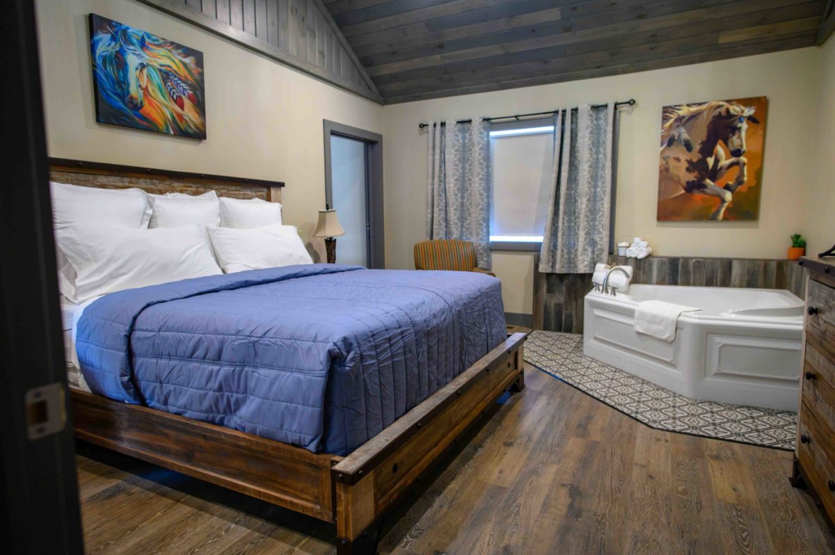 king sized bed with ranch themed bedding and bed frame, jacuzzi, and wood floors and ceilings