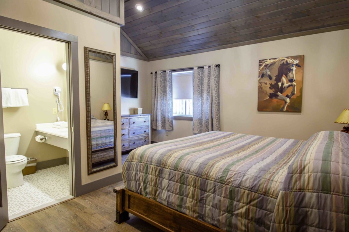 king sized bed with ranch themed bedding and wall art of horse, open to bathroom, hardwood floors and wood plank ceiling