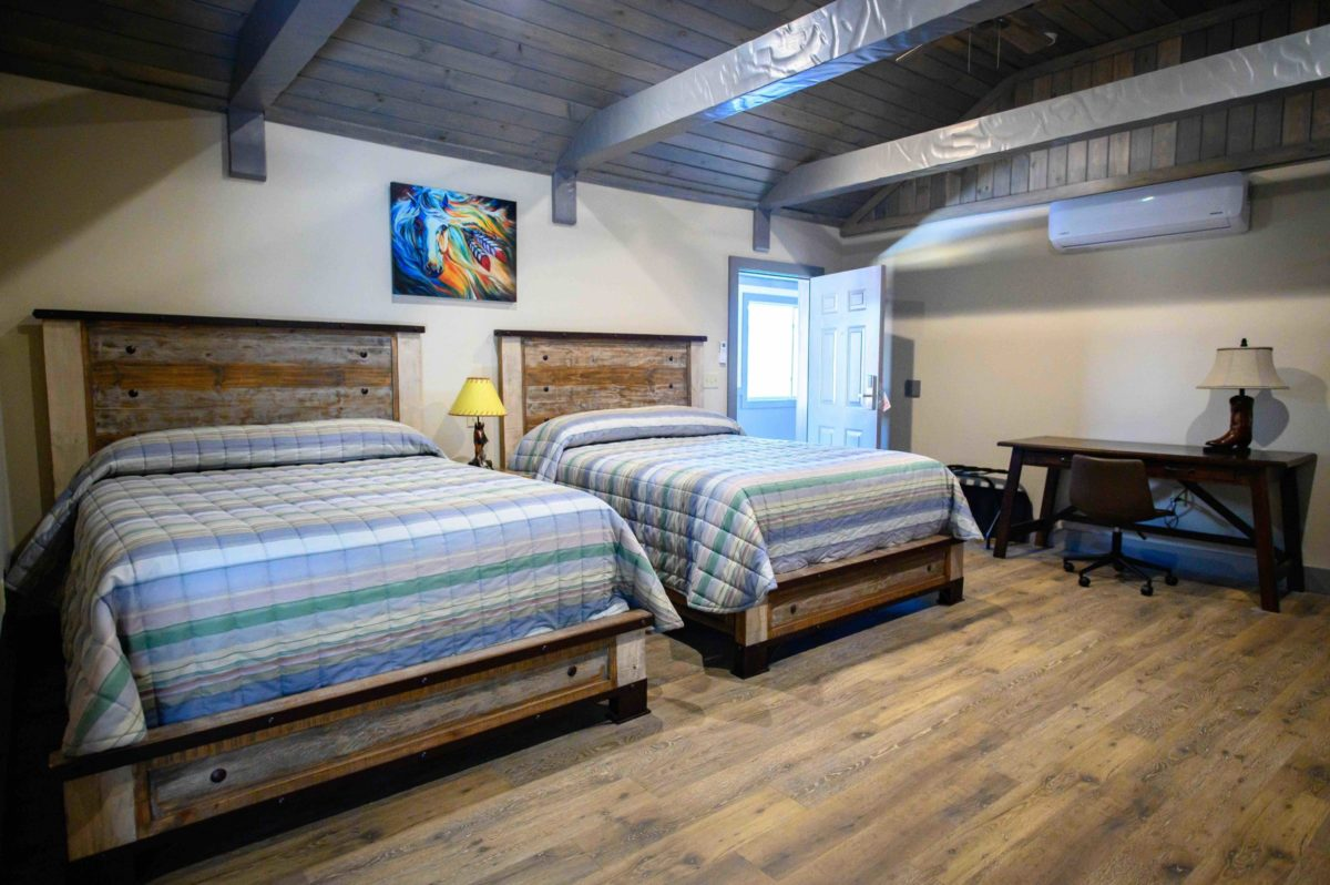 two queen beds with ranch themed bedding, bed frrames and wall art, wood plank ceiling with metal girders