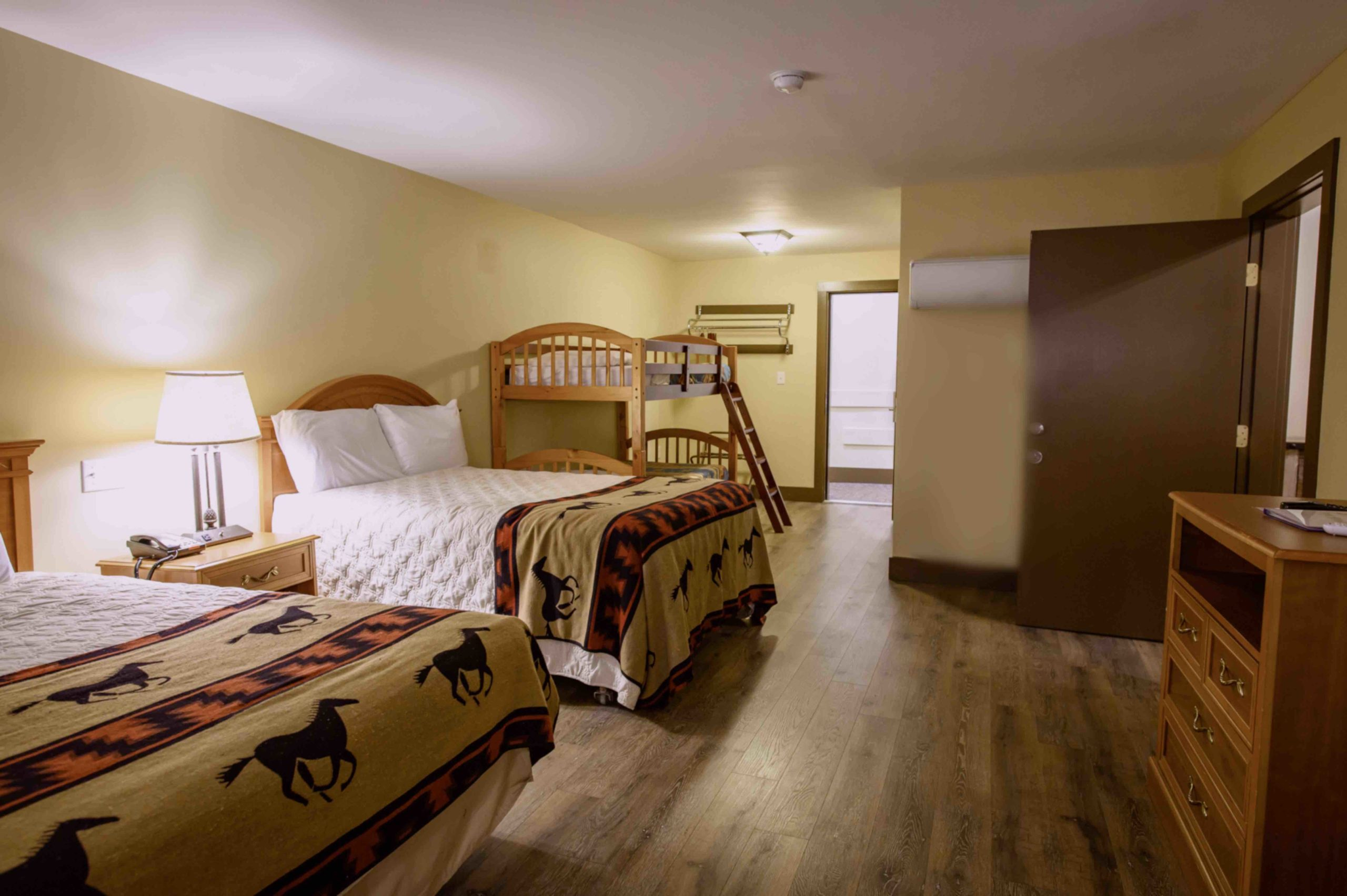 mesa room, two queen beds with horse themed blankets, door entrance to bathroom and to adjoinging room, wooden floors