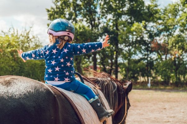 girl riding black horse with helmet on and hands in air