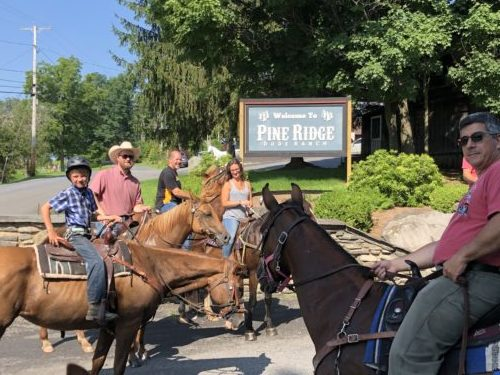 group of people on horseback infront of pine ridge dude ranch main sign