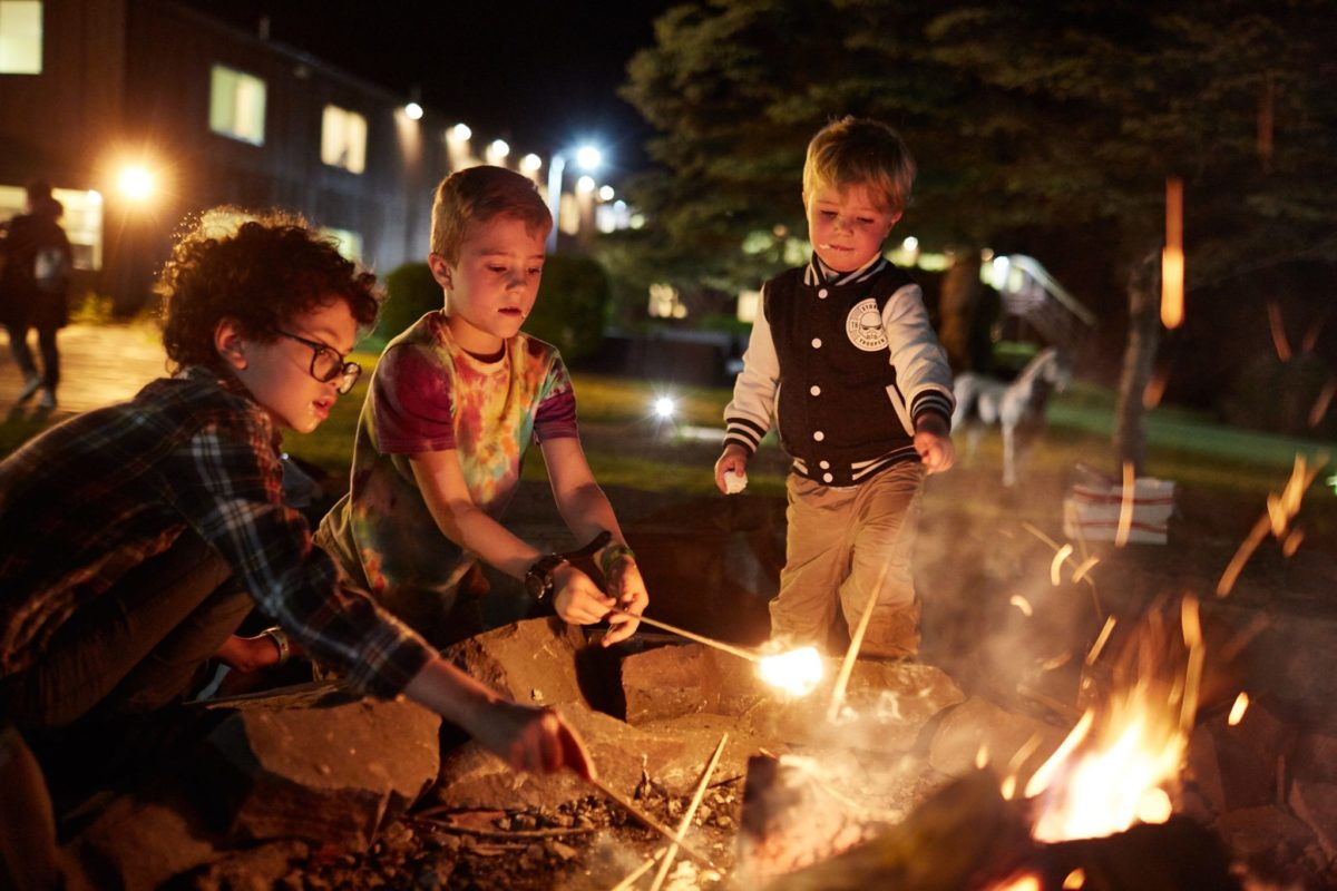 kids around campfire at night roasting marshmellows
