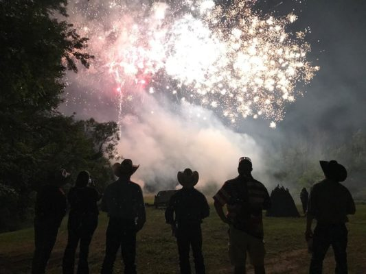 silhouette of cowboys watching fireworks exploding in the sky