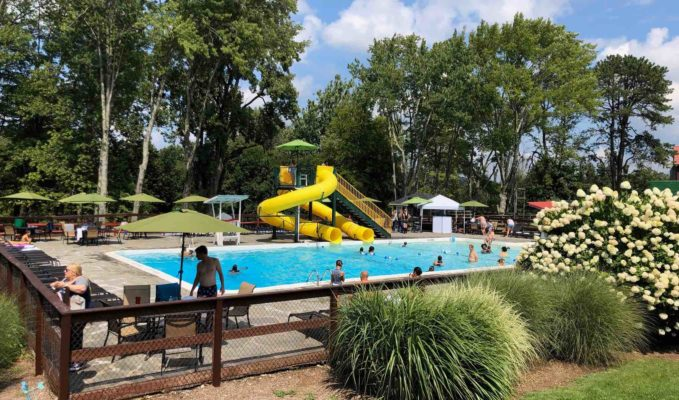 outdoor pool with yellow slide in background and in forest setting